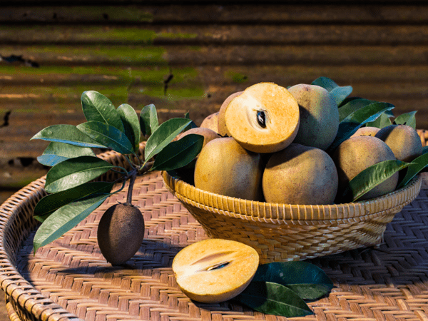 фото корзины с плодами саподиллы на столе